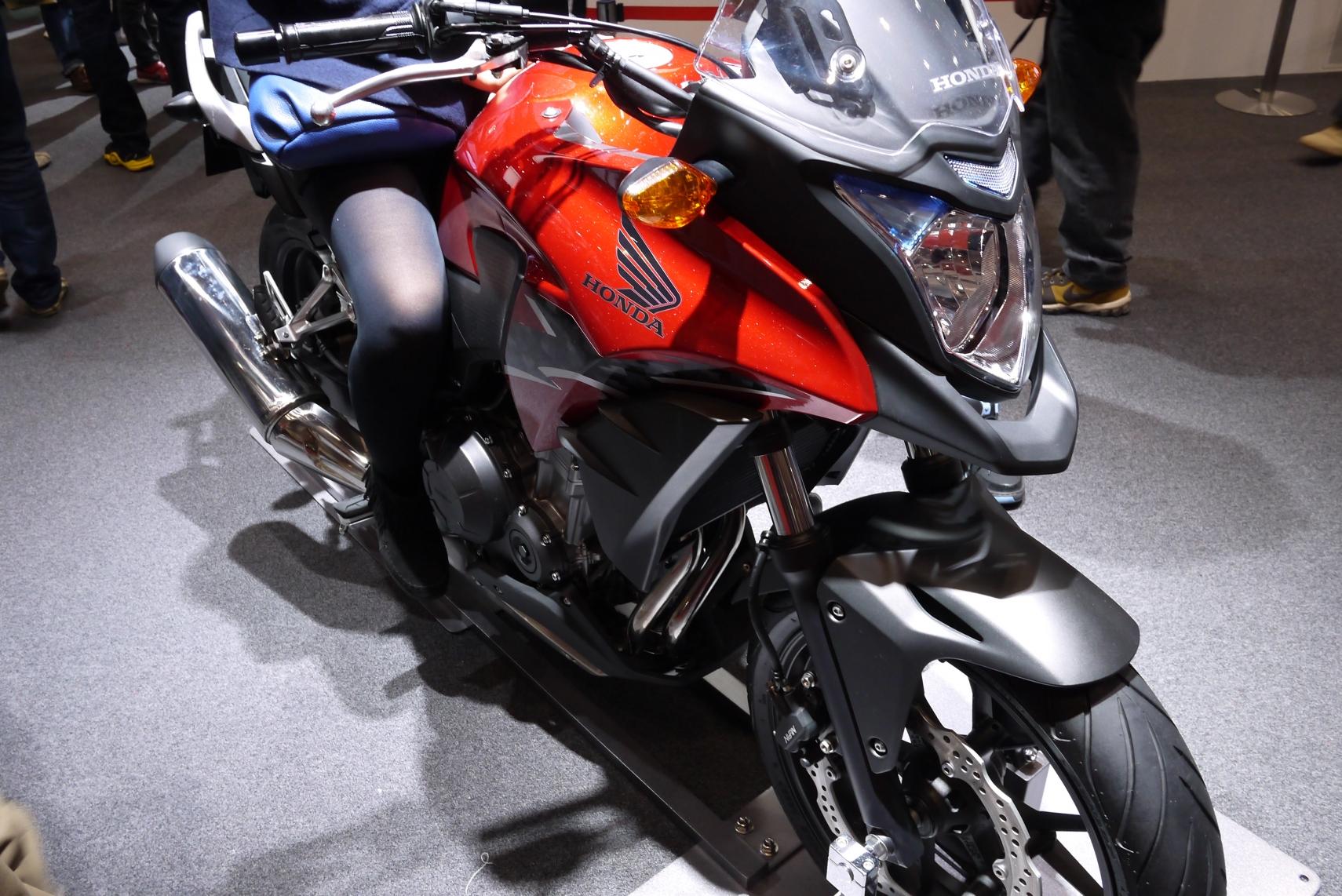 HONDAの赤いカウルのバイクと女性の脚